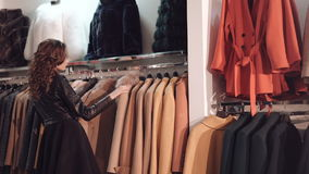 Fashionable lady choosing the rich coats in boutique stock video