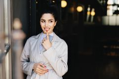 Fashionable lady with dark luminous hair tied in pony tail having nice eyes and red manicure holding her indexfinger on full lips stock photography