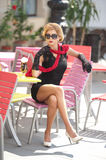 Fashionable  lady with little black dress and red scarf sitting on chair in restaurant, outdoor shot in sunny day. Young blonde Royalty Free Stock Photography