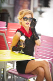 Fashionable  lady with little black dress and red scarf sitting on chair in restaurant, outdoor shot in sunny day. Young blonde Stock Images