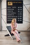 Fashionable lady in pink suit waiting for her flight in airport.