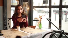 Fashionable lady in red using mobile phone in cafe.