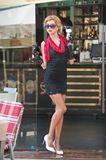 Fashionable lady with short black lace dress and red scarf and high heels, outdoor shot . Young attractive short haired blonde. Fashionable  lady with short Stock Photography