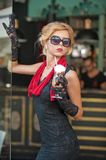Fashionable lady with short black lace dress and red scarf and high heels, outdoor shot . Young attractive short haired blonde Royalty Free Stock Photography
