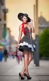 Fashionable lady wearing black hat posing on the street Royalty Free Stock Image