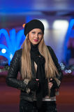 Fashionable lady wearing cap and black jacket outdoor in xmas scenery with blue lights in background. Portrait of beautiful girl Royalty Free Stock Image