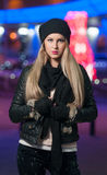 Fashionable lady wearing cap and black jacket outdoor in xmas scenery with blue lights in background. Portrait of beautiful girl stock images