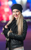 Fashionable lady wearing cap and black jacket outdoor in xmas scenery with blue lights in background. Portrait of beautiful girl Royalty Free Stock Photos