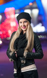 Fashionable lady wearing cap and black jacket outdoor in xmas scenery with blue lights in background. Portrait of beautiful girl stock image