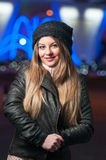 Fashionable lady wearing cap and black jacket outdoor in xmas scenery with blue lights in background. Portrait of young beautiful Royalty Free Stock Images