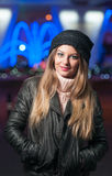 Fashionable lady wearing cap and black jacket outdoor in xmas scenery with blue lights in background. Portrait of young beautiful Stock Images