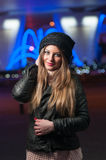Fashionable lady wearing cap and black jacket outdoor in xmas scenery with blue lights in background. Portrait of young beautiful Stock Photo