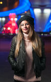 Fashionable lady wearing cap and black jacket outdoor in xmas scenery with blue lights in background. Portrait of young beautiful Royalty Free Stock Photos