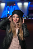 Fashionable lady wearing cap and black jacket outdoor in xmas scenery with blue lights in background. Portrait of young beautiful Stock Photography