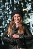 Fashionable lady wearing cap and black jacket outdoor in xmas scenery with blue lights in background. Portrait of young girl Stock Photos