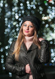 Fashionable lady wearing cap and black jacket outdoor in xmas scenery with blue lights in background. Portrait of young girl Stock Image