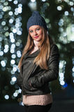 Fashionable lady wearing cap and black jacket outdoor in xmas scenery with blue lights in background. Portrait of young woman Stock Photography