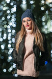 Fashionable lady wearing cap and black jacket outdoor in xmas scenery with blue lights in background. Portrait of young woman Royalty Free Stock Images