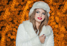Fashionable lady wearing fur cap and coat outdoor. Portrait of young beautiful woman in winter style. Bright picture of girl Royalty Free Stock Images