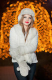 Fashionable lady wearing white fur accessories outdoor with bright Xmas lights in background. Portrait of young beautiful woman. In winter style. Bright picture Royalty Free Stock Photography