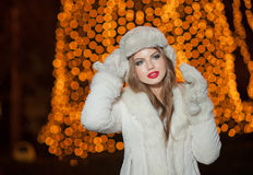 Fashionable lady wearing white fur accessories outdoor with bright Xmas lights in background. Portrait of young beautiful woman Royalty Free Stock Images