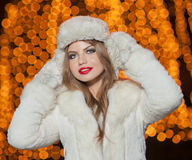 Fashionable lady wearing white fur accessories outdoor with bright Xmas lights in background. Portrait of young beautiful woman Royalty Free Stock Image