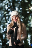 Fashionable lady wearing white fur cap and black muffler outdoor in Xmas scenery with blue lights in background. Portrait of girl Royalty Free Stock Photo