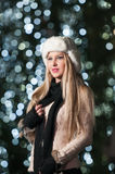 Fashionable lady wearing white fur cap and black muffler outdoor in Xmas scenery with blue lights in background. Portrait of girl Royalty Free Stock Images