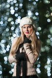 Fashionable lady wearing white fur cap and black muffler outdoor in Xmas scenery with blue lights in background. Portrait of girl stock photography