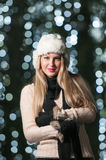 Fashionable lady wearing white fur cap and black muffler outdoor in Xmas scenery with blue lights in background. Portrait of girl Royalty Free Stock Photos