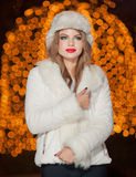 Fashionable lady wearing white fur cap and coat outdoor with bright Xmas lights in background. Portrait of young beautiful woman. In winter style. Bright Royalty Free Stock Photography