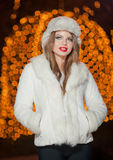 Fashionable lady wearing white fur cap and coat outdoor with bright Xmas lights in background. Portrait of young beautiful woman. In winter style. Bright Royalty Free Stock Photo
