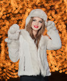 Fashionable lady wearing white fur cap and coat outdoor with bright Xmas lights. In background. Portrait of young beautiful woman in winter style. Bright Stock Photo