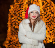 Fashionable lady wearing Xmas hat and white fur coat outdoor. Portrait of young beautiful woman in winter style. Bright Xmas Royalty Free Stock Photo