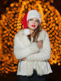 Fashionable lady wearing Xmas hat and white fur coat outdoor. Portrait of young beautiful woman in winter style. Bright Xmas Stock Photos