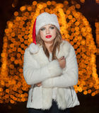 Fashionable lady wearing Xmas hat and white fur coat outdoor. Portrait of young beautiful woman in winter style. Bright Xmas Royalty Free Stock Photography