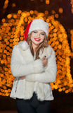 Fashionable lady wearing Xmas hat and white fur coat outdoor. Portrait of young beautiful woman in winter style. Bright Xmas Royalty Free Stock Photos