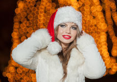 Fashionable lady wearing Xmas hat and white fur coat outdoor. Portrait of young beautiful woman in winter style. Bright Xmas Stock Photo