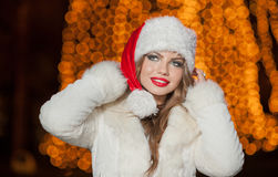 Fashionable lady wearing Xmas hat and white fur coat outdoor. Portrait of young beautiful woman in winter style. Bright Xmas Stock Image