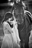 Fashionable lady with white bridal dress near brown horse. Beautiful young woman in a long dress posing with a friendly horse Stock Image
