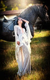 Fashionable lady with white bridal dress near brown horse.   Stock Photos