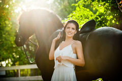 Fashionable lady with white bridal dress near brown horse in nature. Beautiful young woman in a long dress posing with a horse Royalty Free Stock Photography