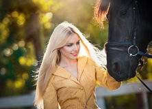 Fashionable lady with yellow coat near black horse in forest.   Royalty Free Stock Images
