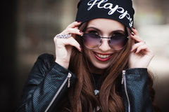 The fashionable laughing young girl in sunglasses Stock Image