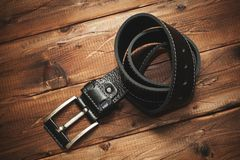 Fashionable leather belt with a buckle on the old wooden background. Personal accessory, piece of clothing Stock Image
