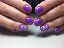 fashionable lilac manicure with a white design stock photo
