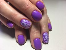 fashionable lilac manicure with a white design royalty free stock image