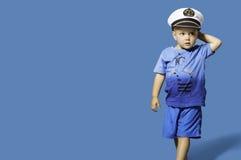 Fashionable little blond boy wearing sailor hat. Blue bacground Stock Photo