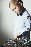 Fashionable Little boy playing chess.Smart kid.Little genius Child. Intelligent game.Chess board Stock Photos