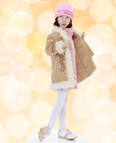 Fashionable little girl in a fur coat. Stock Photos